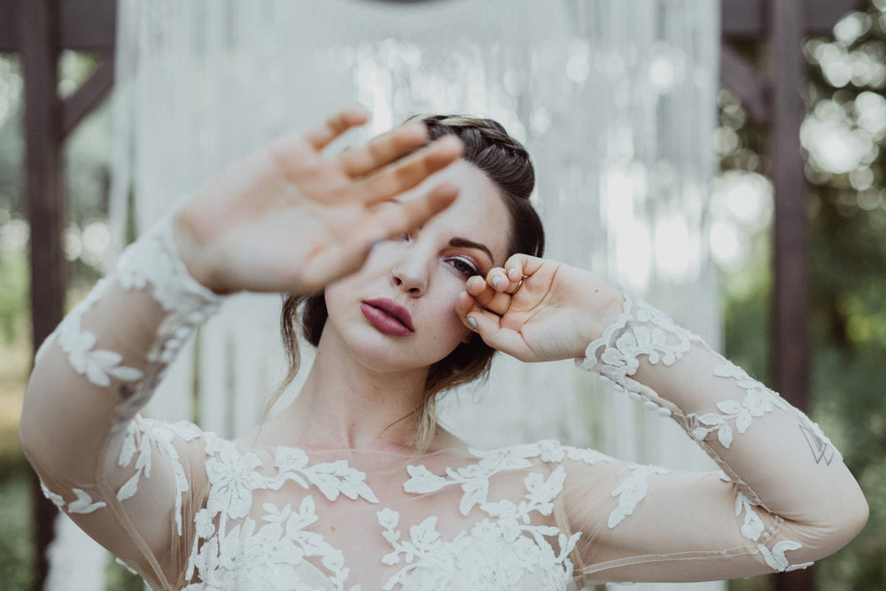 Bride in lace dress in front of macrame