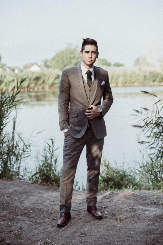 Groom in grey suit standing in front of pond