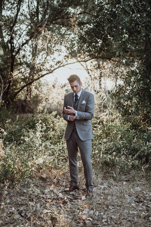 Groom in grey suit standing in grassy field