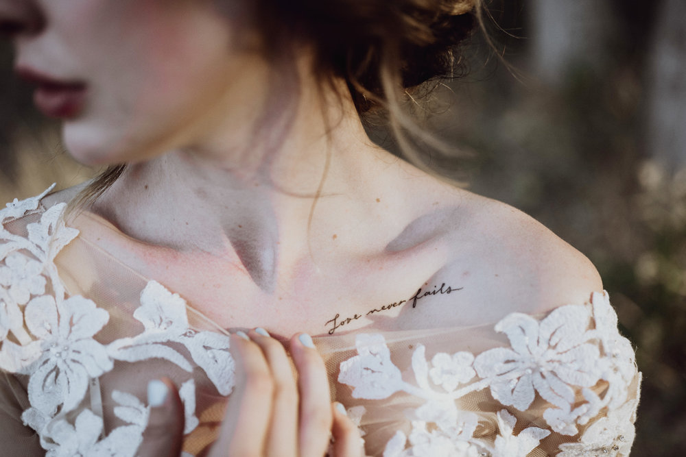 Bride in lace dress with collarbone tattoo