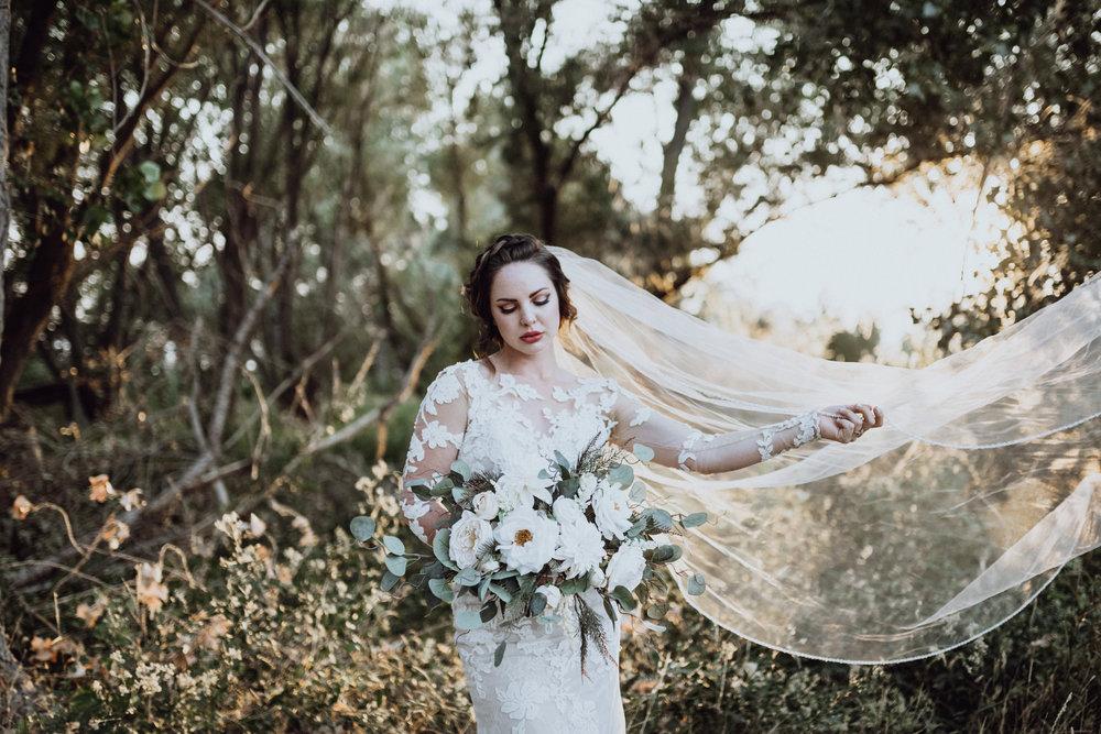 Bride holding bouquet in grassy field