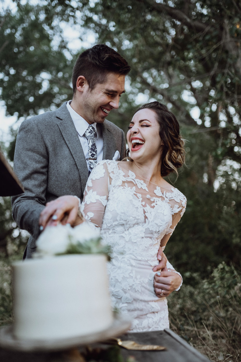 Bride and groom cutting cake in grassy field