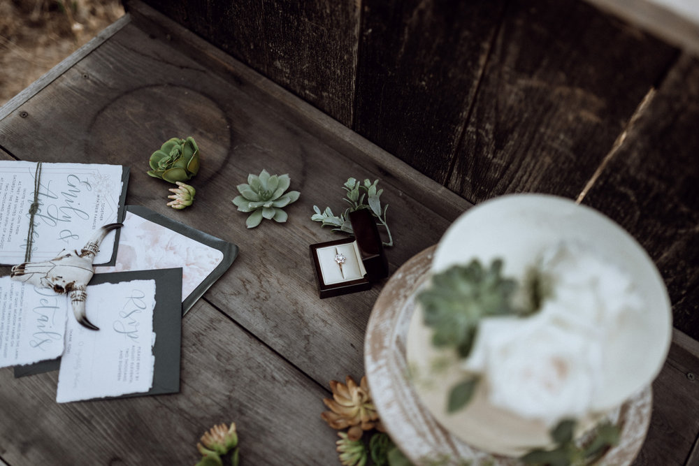 wedding stationary and cake on rustic wooden table