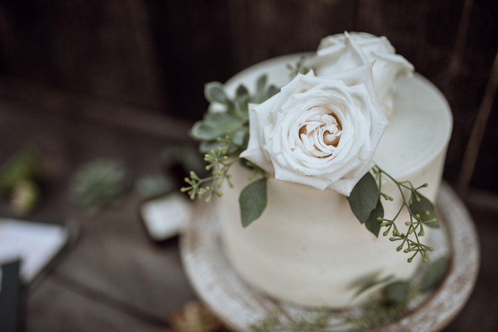 cream wedding cake with flowers and eucalyptus