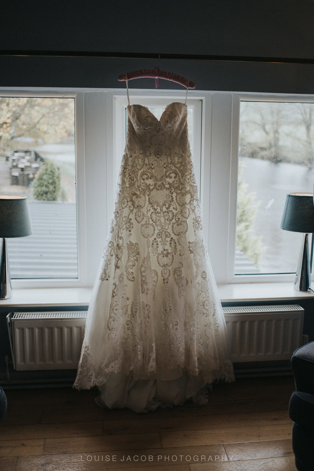 Documentary Wedding Photography - a wedding dress hanging in the window
