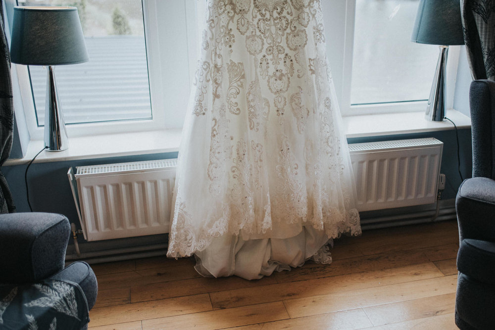 Candid unposed documentary image of a wedding dress hanging in the window