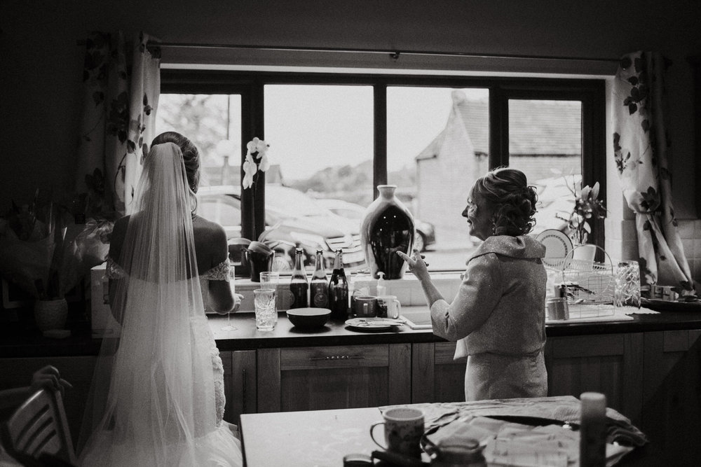 Wedding Photojournalism - A bride and her mum look out of the kitchen window before they leave for the ceremony