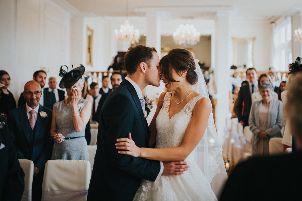 Wedding-photojournalism-groom-kisses-bride-during-ceremony