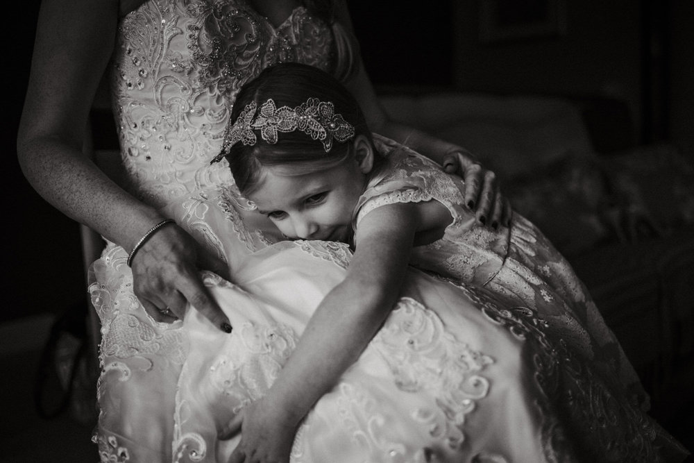 Flower girl hugging a bride