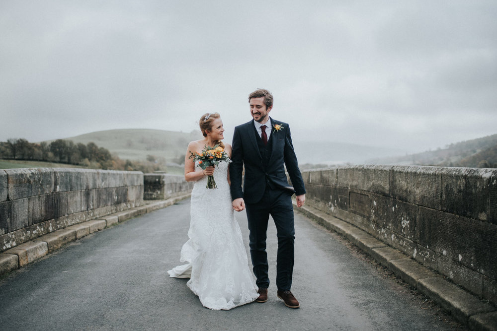 A Bride and Groom walking across a bridge in Burnsall