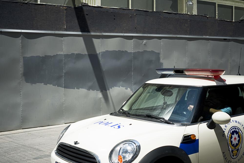 Istanbul juillet 2013. Une voiture de police patrouille dans la rue Istiklal et passe devant un mur repeint par les services de la ville pour recouvrir les tags pro-Gezi. La couleur grise symbolise pour les opposants la volonté de faire disparaître toute trace de Gezi.