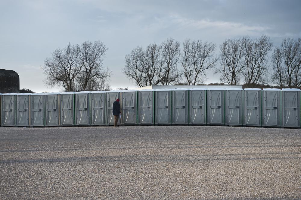 En attendant son ouverture, les migrants son accueilli sur un parking bordé par une rangée de toilettes chimiques.t