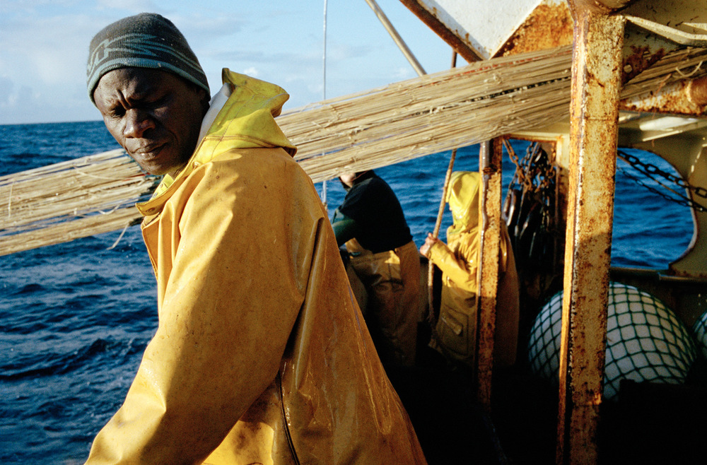 Babacar à l'arrière du bateau lors de la remontée du poisson.   Depuis qu'il a obtenu un permis de séjour, Babacar est en mesure de retourner une fois par an au Sénégal pour rendre visite à sa famille.