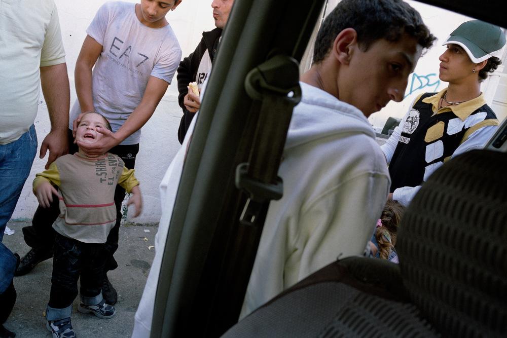 Repas du midi au Faubourg d'Auvergne. Alès, 2008.  Le midi, de retour de l'école, tout le monde mange à la voiture. Rémus et sa femme ainsi que cinq de leurs enfants dorment dans la voiture tous les jours. Les autres sont logés au sein de la communauté roumaine d'Alès.  Adrian est logé chez des amis, ses parents ne veulent pas que les conditions précaires dans lesquelles ils vivent, n'affectent sa réussite scolaire.