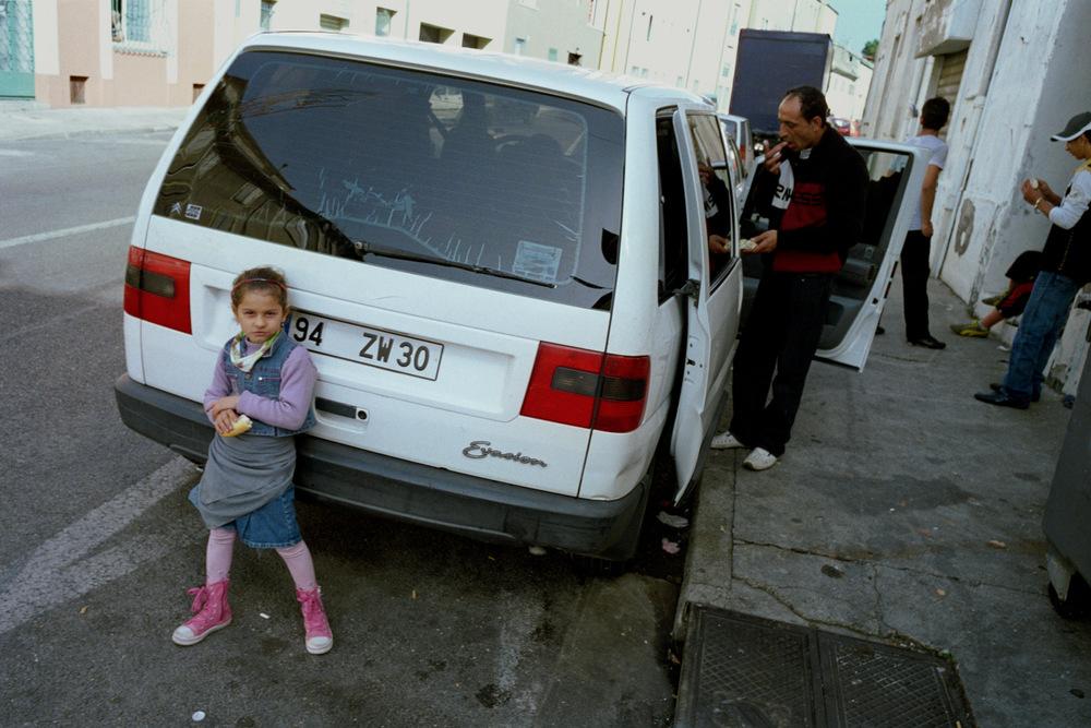 Liliana (la cadette) et Rémus (père).Repas du midi au Faubourg d'Auvergne. Alès, 2008.  Voiture dans laquelle la famille est revenue de Roumanie après l'expulsion, elle est employée à loger une partie de la famille pendant plusieurs mois.  Pour retrouver un logement décent et bénéficier d'aides sociales, Rémus a voulu réouvrir son dossier à la caisse d'allocations familiales. Il apprend qu'ayant reçu «l'aide au retour humanitaire» de l'ANAEM, il est de facto radiédes services sociaux.  Dans les mois qui ont suivi l'expulsion, pendant la période estivale, un décret fût voté empêchant les ressortissants roumains et bulgares d'avoir recours aux aides sociales de la CAF. Romeurope leur confirme cette info.