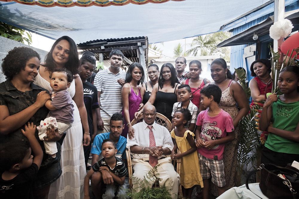 Quartier Combuston, Saint-André. M. Rivière fête ses 80 ans. Toute sa famille s'est rassemblée pour l'évènement. M. Rivière est un descendant d'engagés. Aujourd'hui, les descendants d'engagés comme les autres communautés de l'île se sont mélangés et le peuple de la Réunion forme un grand métissage.