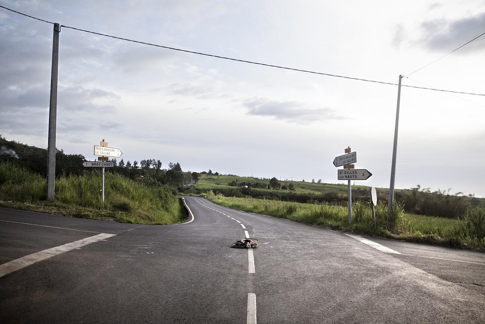 """Villèle, commune de Saint-Paul. Comme pour beaucoup d'autres communautés sur l'île, les Malbars pratiquent de nombreux rites provenant de la sorcellerie. Ici, à l'intersection de deux routes des paniers contenant des poules tuées et des offrandes sont déposés. Appelé """"croisée"""" ou """"saloperie"""", ce rituel à pour but de transmettre le mauvais oeil à l'automobiliste qui roulera dessus."""