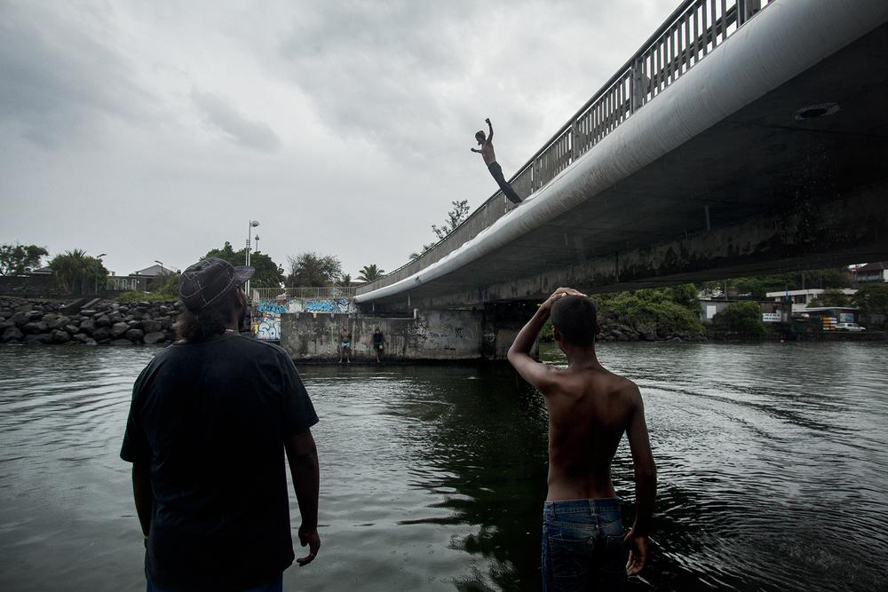 En fin d'après-midi, quelques sans-abris s'amusent sur l'un des petits ponts qui traversent la rivière d'Abord. Un homme saute, bras ouverts. Ses amis l'appellent Guerrier. SAINT-PIERRE, QUARTIER DE TERRE SAINTE, JANVIER 2013
