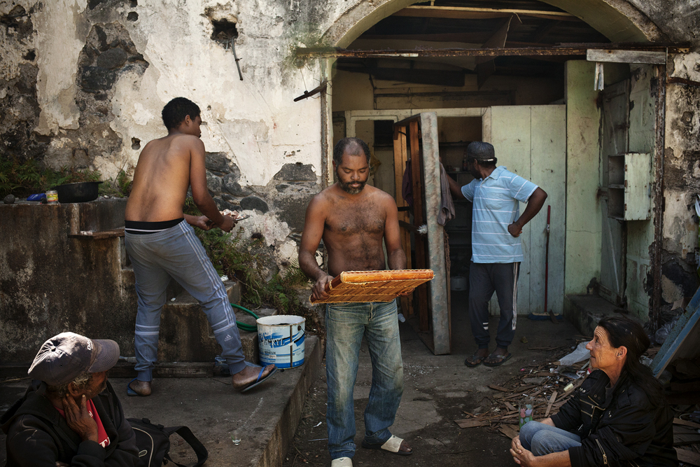 La musique Maloya (musique traditionnelle réunionnaise) résonne dans l'ancien garage désaffecté qui tient lieu de squat à Loulou. SAINT-PIERRE, SQUAT DE LA RAVINE BLANCHE, AOÛT 2014
