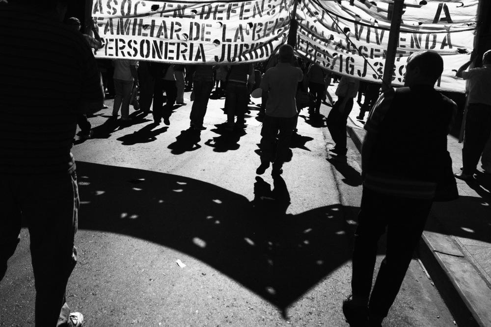 Manifestants dans le quartier des banques à côté de la Plaza de Mayo. Ils font du bruit, ils ne veulent pas que l'on oublie que ces banques, avec la complicité du gouvernement de l'époque (2002), avaient bloqué tous leurs avoirs et ainsi en concomitance avec la fin de la parité Pesos/Dollars, provoqué la ruine d'une grande partie de la population. On a appelé cette période le Corralito, du nom du petit corral, cet étroit couloir par lequel on fait passer les bêtes sur le chemin de l'abattoir.Buenos Aires, décembre 2007