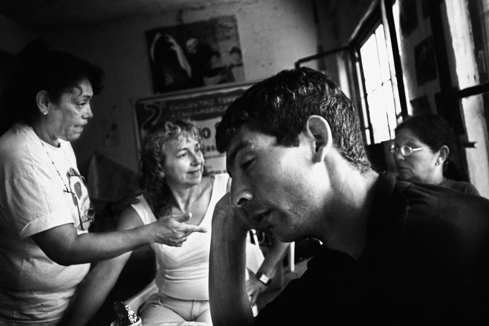 El PACO En 2004, le PACO (Pâte de Cocaïne : drogue constituée de résidus de cocaïne hautement addictive et dangereuse, voire mortelle, qui se fume) est devenu un problème majeur à Buenos Aires pour beaucoup de familles de quartiers pauvres. Etant très peu cher (compter 1 peso=20 centimes d'euros la dose), de plus en plus d'enfants (à partir de 8 ans) en consomment. Des mères ont décidé de réagir, et se sont organisées pour lutter contre ce fléau : Movimiento Madres en Lucha. Elles tiennent des permanences tous les jours au Comedor de los Pibes au coeur du quartier populaire de la Boca. Ici, Marta Gomez (à gauche), présidente du mouvement, discute de l'internement de Jonathan (au premier plan) et de son frère sur la base du volontariat, avec la mère de ce dernier. Jonathan est complètement stone, il dort sur la table. Cette drogue désocialise, coupe la faim, fait des ravages dans les foyers. Les gosses vendent leurs propres vêtements pour pouvoir s'acheter des doses, volent même leur propre famille.Buenos Aires, janvier 2008