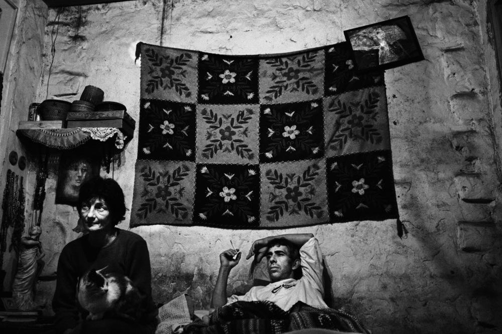 Sandra et Rodrigo En 2002, 50 % de la population argentine était pauvre. Après avoir connu des années beaucoup plus fastes, la chute, notamment pour la classe moyenne, n'en a été que plus dure.Sandra et Rodriguo habitent à Tristan Suarez, à une heure et demie au sud de Buenos Aires. Artistes tous les deux, se considérant comme faisant partie de la classe moyenne avant 2001, et comme économiquement pauvres aujourd'hui, ils n'ont pas eu d'autres choix que de venir habiter dans une petite maison de 25 m2 de deux pièces en province, après avoir habité dans un appartement à Buenos Aires. Ayant chacun un travail, lui jardinier, et elle remplaçante occasionnelle dans des écoles, ils cumulent à eux deux 7 heures quotidiennes de transports en commun pour se rendre et revenir de leur travail, n'ayant pas les moyens d'acheter une moto, et encore moins une voiture… Ils vivent sobrement, dans un confort assez sommaire, mais dignement, sur un bout de terrain pas encore fini de payer. Ils ont trouvé un équilibre de vie dans cette vie « à la campagne » non choisie, et semblent être un couple heureux. Les 300 à 500 euros par mois (quand Sandra travaille) qu'ils gagnent leur permettent tout juste de survivre, mais dans une grande dignité et force morale.Tristan Suarez, janvier 2008