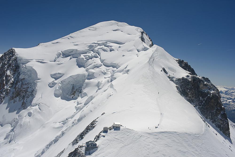 La Voie Normale de l'ascension du Mont Blanc. La cabane Vallo, 4362 m d'altitude (En bas de l'image) est le dernier abri ( non gardé) avant e sommet ( en haut de l'image) du Mont Blanc à 4810 m d'altitude. En été, les missions de secours du PGHM de Chamonix  autour de l'ascension du Mont Blanc représente la majeur partie des secours. A cette altitude, chaque mission peut s'averer périlleuse. Le vent peut notamment empecher à une caravanne de secours d'étre déposer en helicoptère et la contrainte à acceder à une zone de secours par voie terrestre et la rendre ainsi beaucoup plus longue. Au départ de Chamonix, il ne faut que quelques minutes à un helicoptère pour accéder à cette zone.