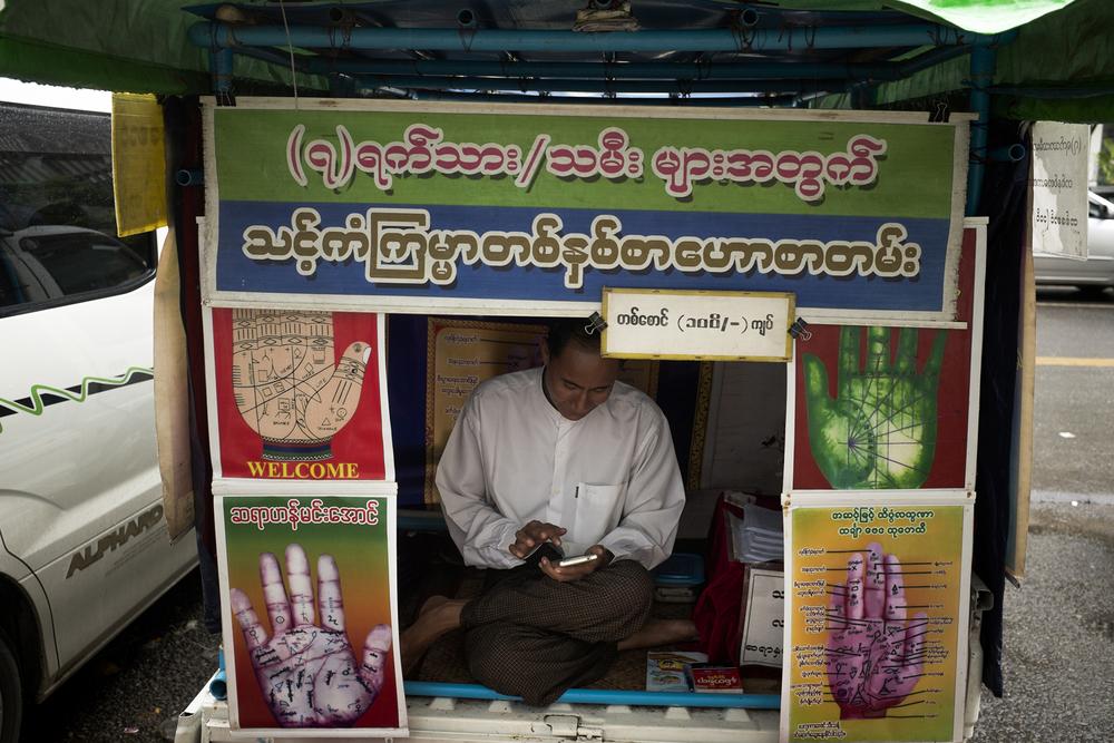 Un astrologue officiant dans la rue près de la pagode Sule, connue pour ses astrologues. Rangoun, Birmanie, Mai 2015.