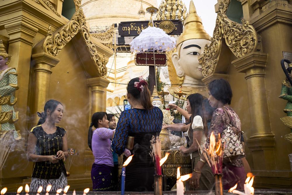 """Ces jeunes femmes se recueillent sur l'autel du """"dimanche"""". En Birmanie le signe astrologique, le nom porté dépend du jour de la naissance. Rangoun,  Birmanie, Mai 2015."""