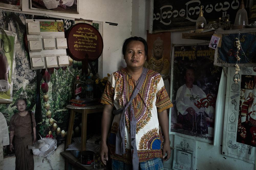 Kaung Si Thu. Cet astrologue réputé dans les environs s'est formé avec un maître à Rangoun. Il exerce seul dans son cabinet plein à craquer d'offrandes, d'objets entassés et de posters d'astrologues. New Bagan, Birmanie, Mai 2015