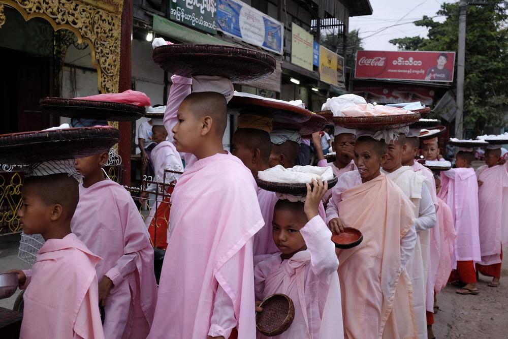 Comme tous les matins, ces nonnes vont récolter les offrandes des habitants en procession de le village. Birmanie, Mai 2015.