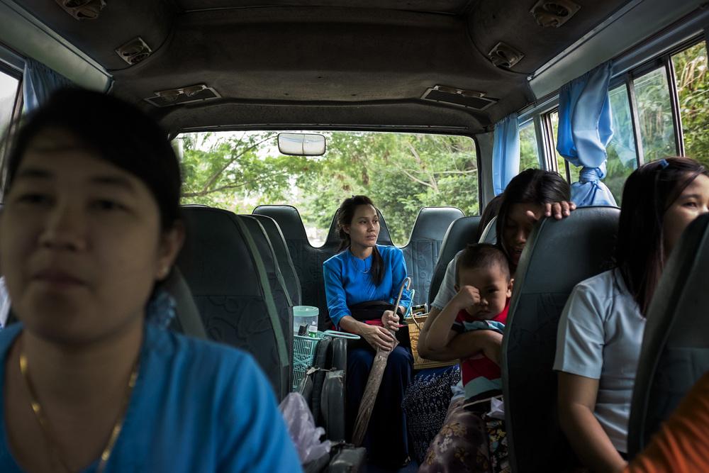 Des employées d'un des hopitaux de la ville dans le bus qui les ramène dans les ensembles de logement où elles vivent. Naypyidaw, Birmanie. Mai 2015.