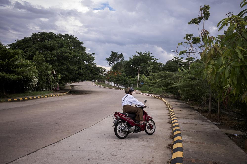 Un motard dans l'une des avenues vides d'un quartier résidentiel de la ville. Naypyidaw, Birmanie. Mai 2015.