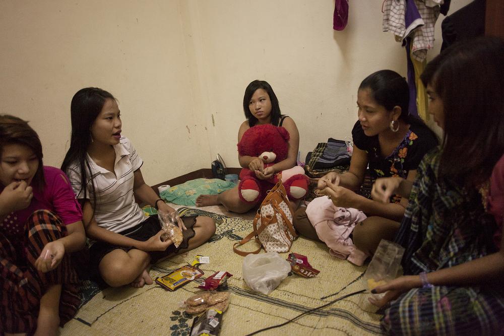 Hnin Hnin, la maquerelle (4ème en partant de la gauche) qui gère le business se rend dans la maison pour s'entretenir avec les filles qu'elle emploie. Elle limite ses visites et préfère utiliser le téléphone pour communiquer avec les filles.Mae Sot, Thailande. Octobre 2014,