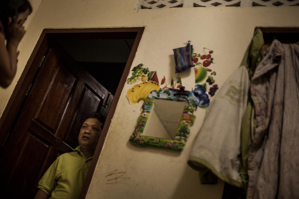 Malgré la confidentialité de la maison, quelques clients savent que des prostitués y vivent. Cet homme Thaïlandais essaie tant bien que mal de décrire la fille avec qui il était parti lors de sa dernière visite. Mae Sot, Thailande. Octobre 2014,