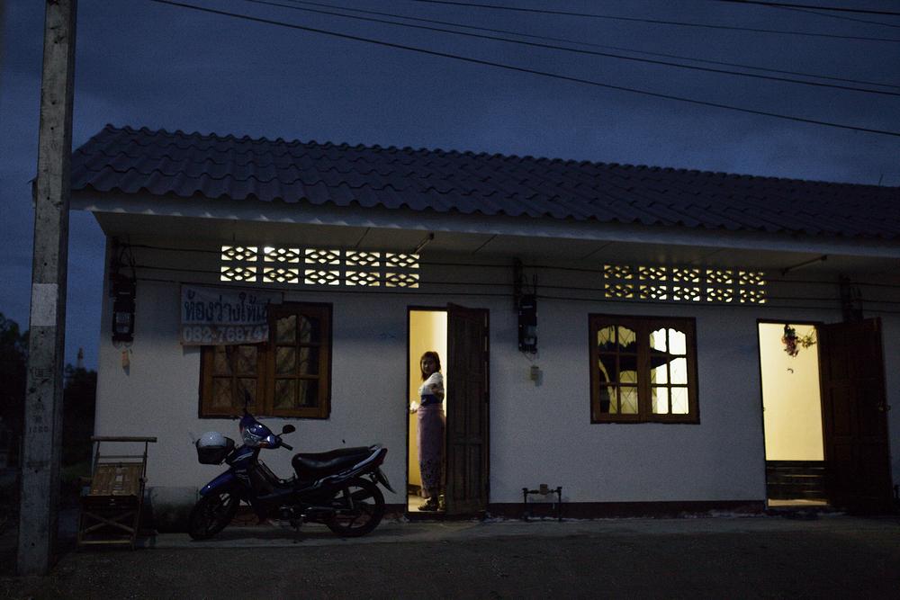 Une prostituée rentre dans la maison qu'elle partage avec 8 autres filles. Leur maquerelle les loge à cet endroit et emploie des taxis pour les amener dans les hotels de la ville. Mae Sot, Thailande. Octobre 2014,