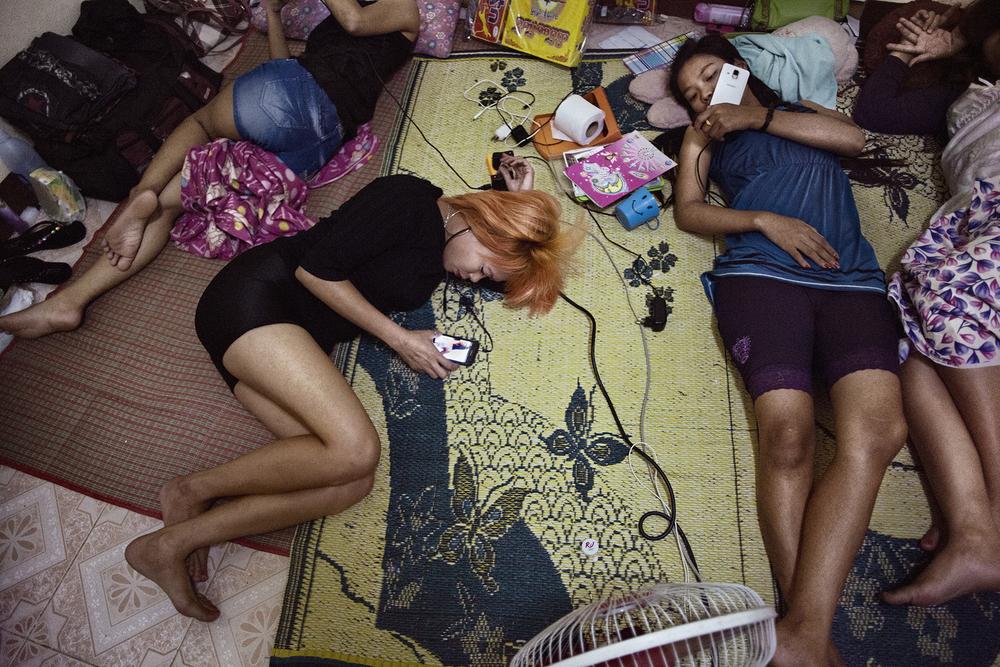 Les filles dorment à cinq en moyenne dans cette pièce. Elles y passent le plus clair de leur temps mis à part quelques rapides sorties pour acheter à manger ou pour rejoindre un client dans un hôtel de passe. Mae Sot, Thaïlande, novembre 2014