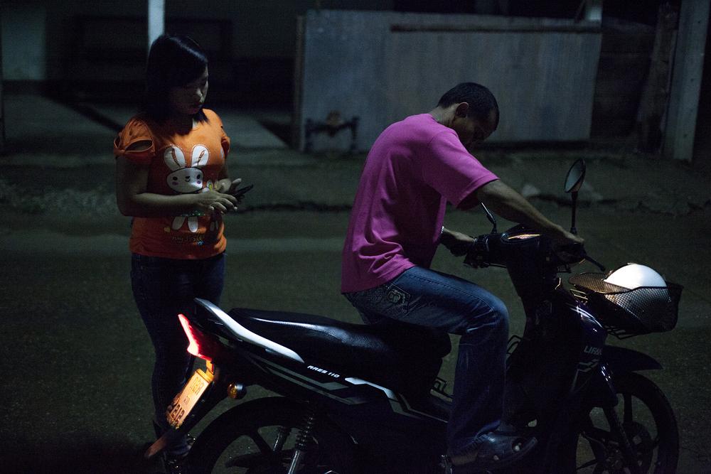 Une prostituée part en scooter à un rendez vous avec un client.Mae Sot, Thailande. Octobre 2014,