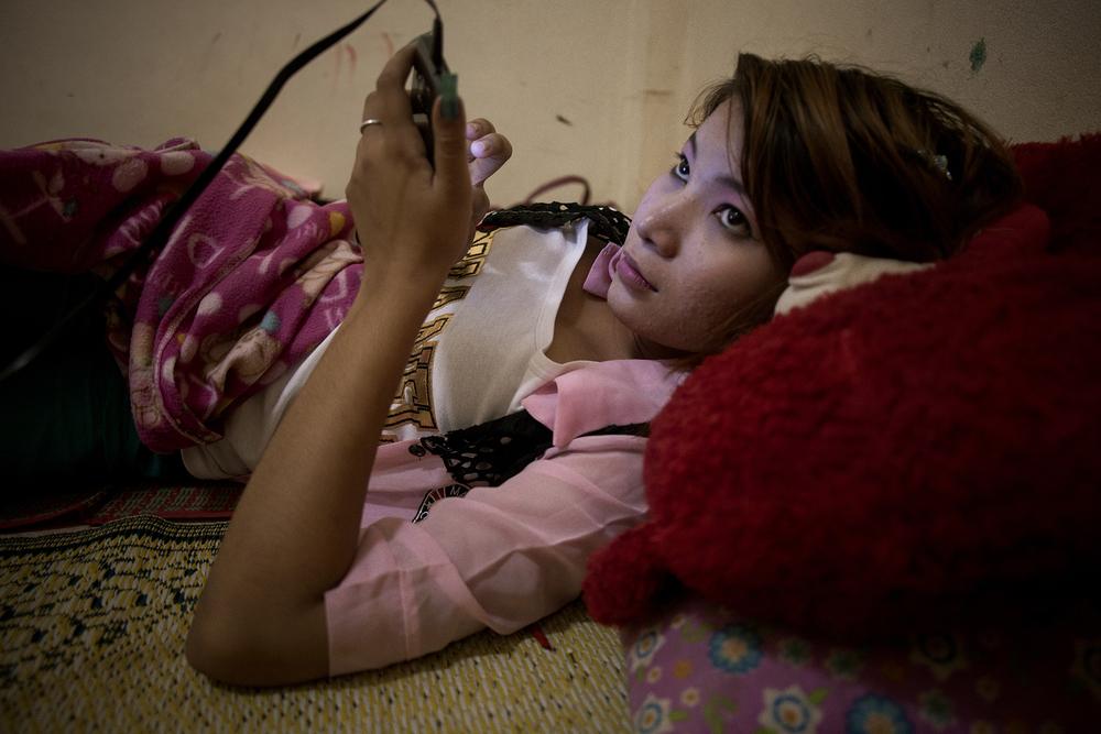 Nay Ji au téléphone avec son copain Les femmes qui exercent cette profession sont stigmatisées dans la culture Birmane. La plupart des prostituées à Mae sot évitent les marchés, les restaurants par peur des regards. Cette stigmatisation les enferment dans les réseaux de la prostitution. Mae sot, Thailande. Octobre 2014.