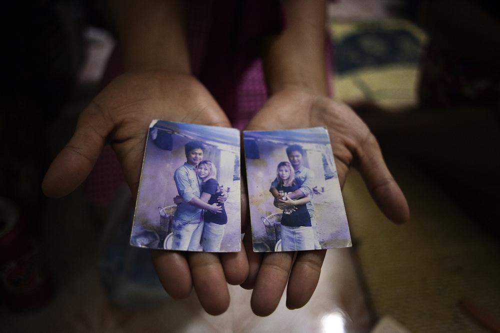 Une prostituée montrant une photo d'elle en compagnie de son petit ami resté en Birmanie. La plupart des filles sont en couple mais elles voient très rarement leurs compagnons. Les familles, auxquelles elles envoient de l'argent ne sont pas au courant de ce que font leurs filles et pensent qu'elles travaillent comme serveuses ou ouvrières.Mae Sot, Thaïlande, octobre 2014