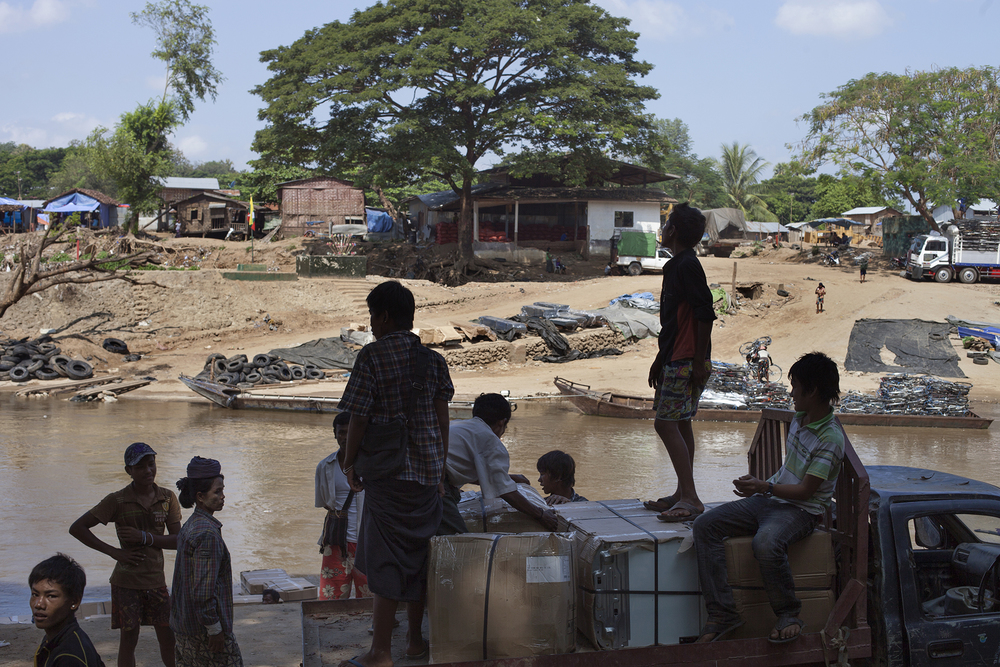 Des porteurs attendent la barge pour faire passer des marchandises du côté birman de la rivière Mo Ei. Cette rivière court sur 327 km entre les deux pays. Cette frontière extrêmement poreuse est connue pour être le lieu de tous les trafics : marchandises, drogue, être humains. Selon les estimations, près d'un million de Birmans vivent le long de cette frontière côté thaïlandais. Mae Sot, Thaïlande, octobre 2013