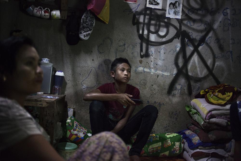 Des travailleurs migrants regardent la télévision dans la pièce qui leur sert de chambre. Les patrons des usines logent souvent les ouvriers sur place dans des locaux exigus: insalubres, sans aération, l'électricité y est limitée aux horaires de nuit, entre 18 h et 6 h du matin. Mae Sot, Thaïlande, novembre 2013