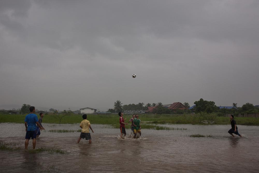 Des jeunes hommes jouent au football pendant une averse de mousson. Le football et notamment le championnat anglais sont très populaires chez les Birmans. Mae Sot, Thaïlande, juillet 2011
