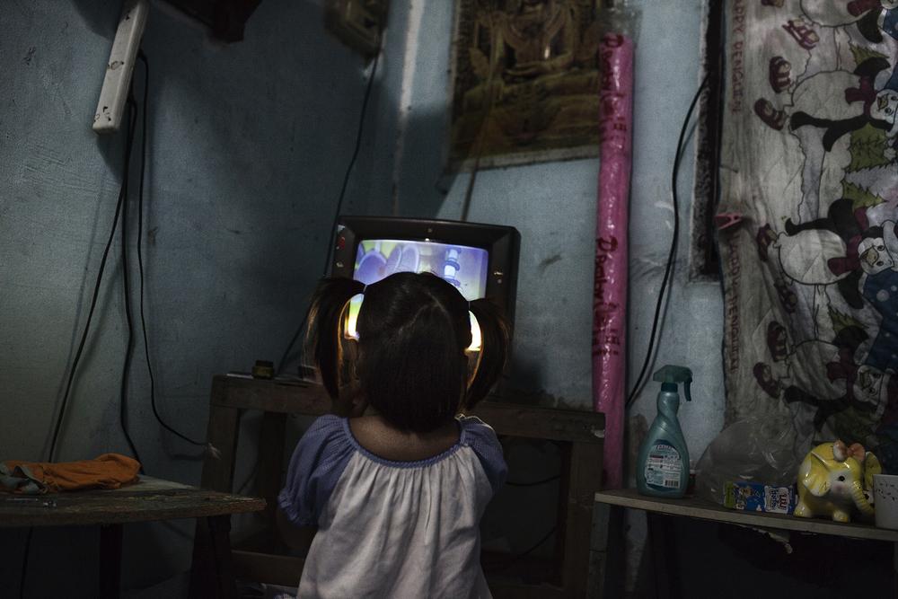 Ei Ei Htwe, 6 ans, est livrée à elle-même tous les soirs pendant que sa mère travaille dans un karaoké. La solidarité locale permet à Hayman de demander aux voisins de garder un œil sur sa fille quand elle est absente.Mae Sot, Thaïlande, octobre 2014