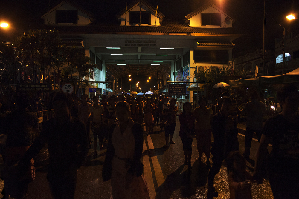 Une foule de Birmans viennent de traverser le pont de l'amitié qui relie la ville de Myawwady en Birmanie à la Thaïlande. Les autorités thaïlandaises laissaient passer les Birmans ce soir-là en raison de la tenue du festival Loy Kratong. Mae Sot, Thaïlande, octobre 2014