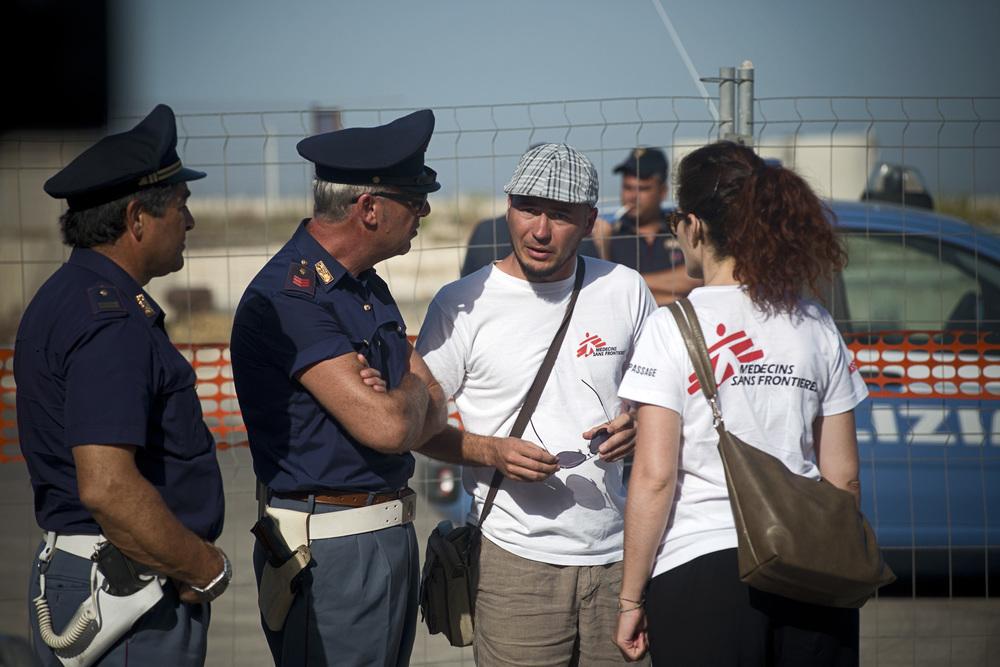 03- Exceptionnellement, la police italienne, à la demande de la justice, a établit un périmètre de sécurité sur le bout de quai isolé qui accueille l'Aquarius dans le port sicilien. Les journalistes italiens venus en nombre sont tenus à l'écart. Seuls les membres de la protection civile italienne, de la Croix Rouge, et de Médecins Sans Frontières sont autorisés à venir au plus près du navire, à la rencontre de ceux qu'ils vont bientôt prendre en charge.