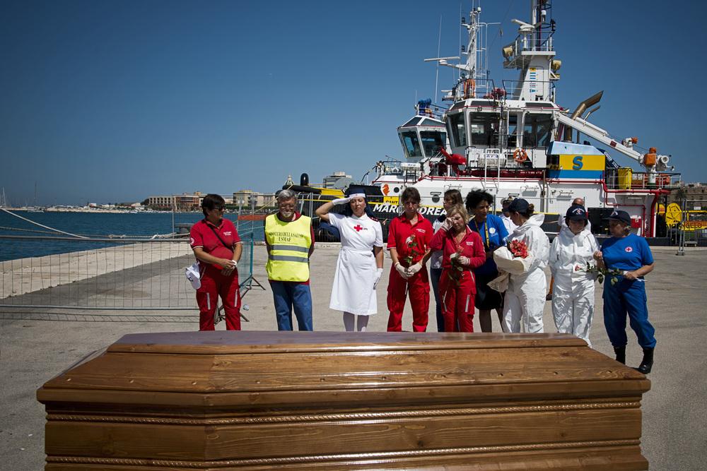 10- A terre, des membres de la Croix Rouge italienne et une représentante des infirmières auxiliaires de l'armée rendent hommage aux victimes en déposant une rose sur chaque corps avant que le cercueil ne soit refermé.  Un geste destiné à rendre un peu de  dignité à ces personnes qui n'ont jamais finit leur voyage vers l'Europe.