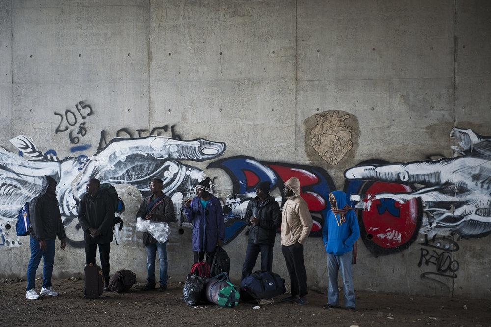 Des départs de la Jungle s'organisent discrètement en ce matin pluvieux du 18 octobre. Ce groupe d'exilés attend à l'abri d'un pont d'être emmené en voiture par des bénévoles. Ils ne partent pas pour un Centre d'Accueil Provisoire, mais vers le campus de Villeneuve d'Asque. En mars dernier, un professeur un peu «rêveur» de l'université Lille 3, «une artiste passionnée,  un groupe de migrants enthousiasmés à l'idée de reprendre leurs études,  l'Auberge des Migrants et  la Cabine Juridique» ont imaginé créer une classe de français langue étrangère dédiée aux exilées. Cette classe s'appelle le Défi comme le rappelle l'association sur sa page Facebook.