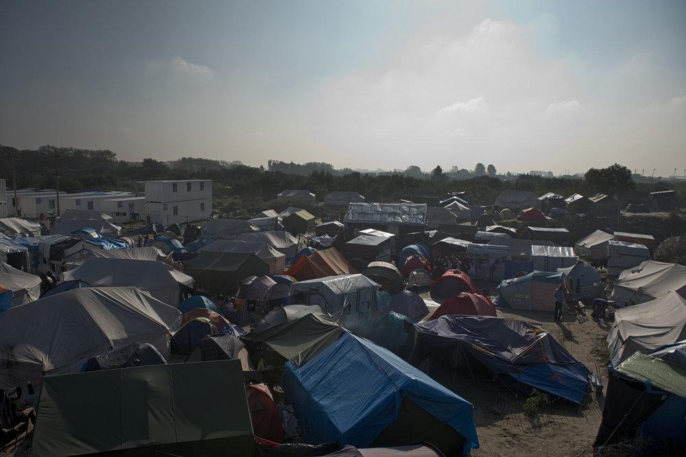 """Calais, dimanche 23 octobre 2016. Le soleil se couche sur la cité de tentes, de cabanes et de conteneurs qui a abrité jusqu'à 10 000 migrants à la périphérie de la ville de Calais. Après dix-neuf mois d'existence, la """"jungle"""" est à son crépuscule et vit ses derniers moments d'autogestion avec l'aide de dizaines d'associations, d'ONG et de milliers de bénévoles qui se sont relayés un jour, une semaine, un mois pour apporter un peu d'humanité dans ce territoire délaissé de la République."""