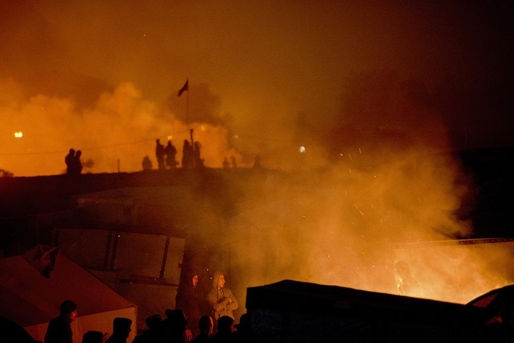 Calais. Au soir du deuxième jour du démantèlement, le bidonville s'illumine de multiples feux. Les braseros s'alimentent avec des bouts de cabanes désertées et dépecées. Détruire par le feu ce que l'on doit abandonner est même une « tradition héritée du démantèlement de la zone en mars dernier », assure Fabienne Buccio, la préfète du Pas-de-Calais. La veille, des groupes de jeunes Afghans refusant de renoncer à leur rêve d'Angleterre avaient protesté en défiant la police à coups de pierre et en allumant des premiers feux sur la zone des 100 mètres, qui sépare le campement de la Lande et la rocade portuaire.